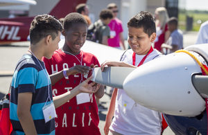 Three middle schoolers with model airplanes
