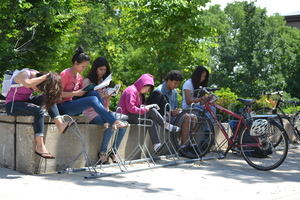 High schoolers reading and sitting on a bench