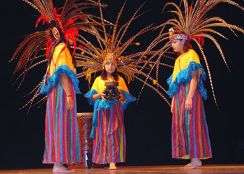 Three children performing an Aztec dance